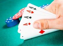 Cartões de jogo em uma mão do homem na frente das fichas Foto de Stock Royalty Free