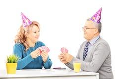 Cartões de jogo maduros dos pares na tabela em um partido imagem de stock royalty free
