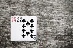 Cartões de jogo quatro dez na tabela de madeira Fotografia de Stock Royalty Free