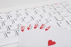 Cartões de jogo que encontram-se no teclado de computador Fotos de Stock Royalty Free
