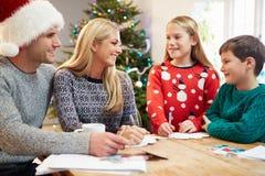 Cartões de Natal da escrita da família junto Fotografia de Stock
