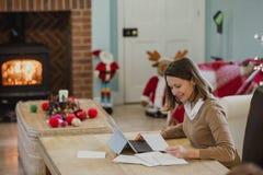 Cartões de Natal da escrita da mulher em casa Imagem de Stock