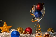Cartões de Natal Vidro de vinho com as decorações vermelhas, do azul e do ouro do Natal foto de stock royalty free