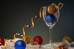 Cartões de Natal Vidro de vinho com as decorações vermelhas, do azul e do ouro do Natal fotografia de stock royalty free