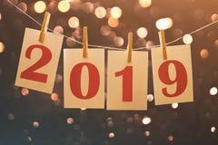 2019 cartões de papel de ano novo que penduram na corda com luzes borradas no fundo fotos de stock