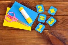 Cartões de papel com números, tesouras, folhas de papel, colagem em um fundo de madeira marrom Conceito da instrução Foto de Stock Royalty Free
