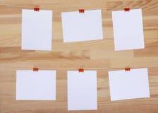 Cartões de papel vazios unidos com a braçadeira colorida na corda de linho no fundo da placa de madeira, em moldes vazios para im fotos de stock