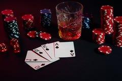Cartões do jogador de pôquer Na tabela são as microplaquetas e um vidro do cocktail com uísque Combinação de cartões - resplendor Foto de Stock Royalty Free