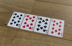 Cartões do pôquer em um backround de madeira, no grupo de dez dos clubes, nos diamantes, nas pás, e nos corações Fotografia de Stock Royalty Free
