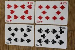 Cartões do pôquer em um backround de madeira, no grupo de dez dos clubes, nos diamantes, nas pás, e nos corações Imagem de Stock