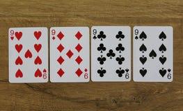 Cartões do pôquer em um backround de madeira, no grupo de nines dos clubes, nos diamantes, nas pás, e nos corações Imagens de Stock Royalty Free