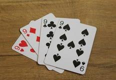 Cartões do pôquer em um backround de madeira, no grupo de nines dos clubes, nos diamantes, nas pás, e nos corações Fotos de Stock Royalty Free
