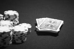 Cartões do pôquer e microplaquetas da aposta em um jogo de tabela Fotos de Stock