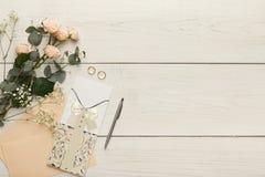 Cartões e envelopes do convite do casamento na tabela de madeira branca, vista superior Fotografia de Stock Royalty Free