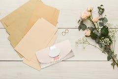 Cartões e envelopes do convite do casamento na tabela de madeira branca, vista superior Foto de Stock Royalty Free