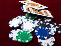 Cartões e microplaquetas de pôquer em um fundo vermelho Foto de Stock Royalty Free