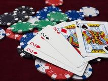 Cartões e microplaquetas de pôquer em um fundo vermelho Fotografia de Stock