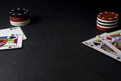 Cartões e microplaquetas do pôquer no preto Cabeças acima, pares de reis imagem de stock