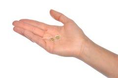 Cartões nano da posse 2 SIM da mão isolados Fotografia de Stock Royalty Free