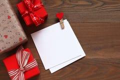 Cartões para escrever dos desejos em uma tabela de madeira com presentes Imagens de Stock