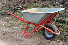A cart for carrying heavy cargo in the garden. A cart for carrying  cargo in the garden in spring Royalty Free Stock Image