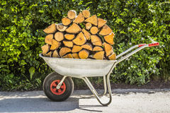 The cart with firewood. The trolley is fully loaded with firewood close-up Royalty Free Stock Photography