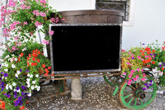 Cart with flowers. And table information Royalty Free Stock Photography