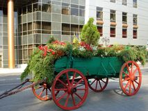 Cart with flowers. Wooden cart decorated with flowers and green branches, placed in front of the registry office, as a setting for wedding photos Royalty Free Stock Photos