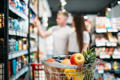 Cart with fresh fruits in food store. Couple looks at the pruducts on background. Customers or buyers in supermarket stock images