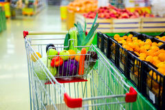 Cart with fresh fruits and vegetables in shopping centre Royalty Free Stock Images