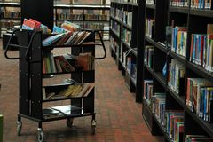 A cart and shelves with books in different colours in the library. A cart full of books between bookcases with all kind of books is still waiting in the Royalty Free Stock Images