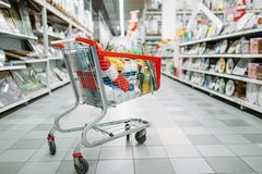 Cart full of goods in supermarket, nobody. Shopping concept. Trolley with products in market, no people royalty free stock photo