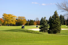 Cart Golfers On The Fairway. An autumn golfing vacation in Wisconsin. Golfers with golf cart on the fairway Stock Photography