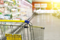 Cart at the grocery store. Abstract blurred photo of store with trolley in department store bokeh background. New ideas in trade and business.Advertising of Stock Photos