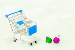 Cart from the grocery store and decorations on the snow. Concept of winter shopping. New Year and Christmas buying. Cart from the grocery store on snow. Concept Royalty Free Stock Photo