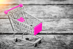 Cart from the grocery store on the old wooden background. Empty shopping trolley. stock photography