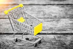 Cart from the grocery store on the old wooden background. Empty shopping trolley. Business ideas and retail trade. Advertising of food products Stock Photo