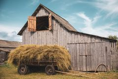 Old cart with hay on the background of the hay. Cart with haya cart with hay on the background of the barn. preparation for harvesting in the hayloft for storage Royalty Free Stock Photo