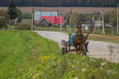 A cart with a horse in a Russian village. Stock Photography