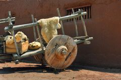 Cart With Huge Wooden Wheels. Mexican cart has huge wooden wheels and wooden hubs.  Cart sits in front of an adobe home Royalty Free Stock Photography