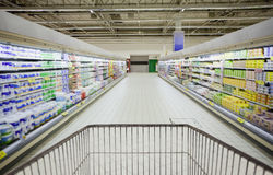 Cart in supermarket. Cart in super market aisle Royalty Free Stock Photo