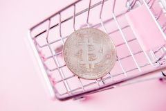 A cart from a supermarket, bitcoin on a wooden background. internet, crypto currency.  stock photos