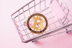 A cart from a supermarket, bitcoin on a wooden background. internet, crypto currency.  royalty free stock photos