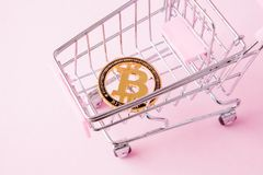 A cart from a supermarket, bitcoin on a wooden background. internet, crypto currency.  stock image