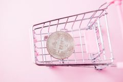 A cart from a supermarket, bitcoin on a wooden background. internet, crypto currency.  stock images