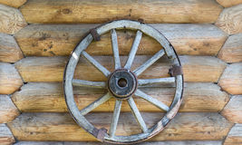 Cart wheel on log wall Stock Image