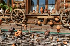 Cart wheels and ceramic pots hanging on a village house wall. Wattle fence at bottom. stock photo