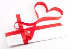 Carta atada con una cinta roja bajo la forma de corazón Imagen de archivo