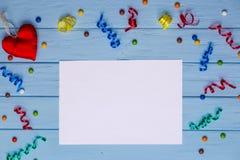 Carta in bianco bianca con i nastri variopinti intorno ed il cuore fatto a mano Fotografia Stock