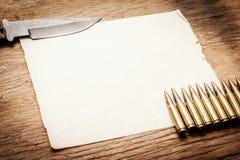 Carta in bianco, coltello e pallottole Immagine Stock